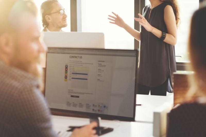 Computerbildschirm im Vordergrung, im Hintergrund findet ein Gespräch zur Personalvermittlung statt